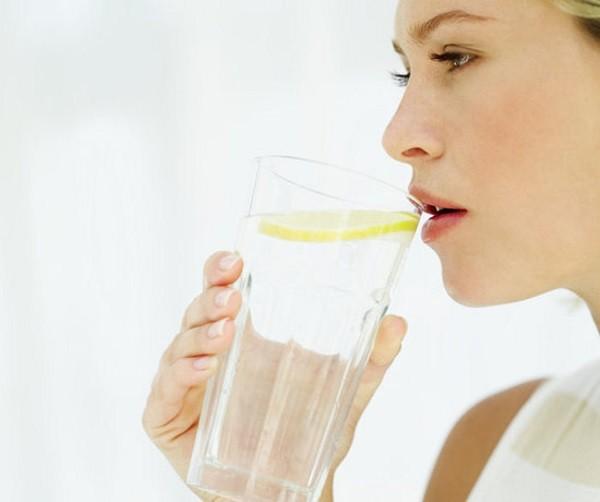 Κοπέλα πίνει νερό με λεμόνι